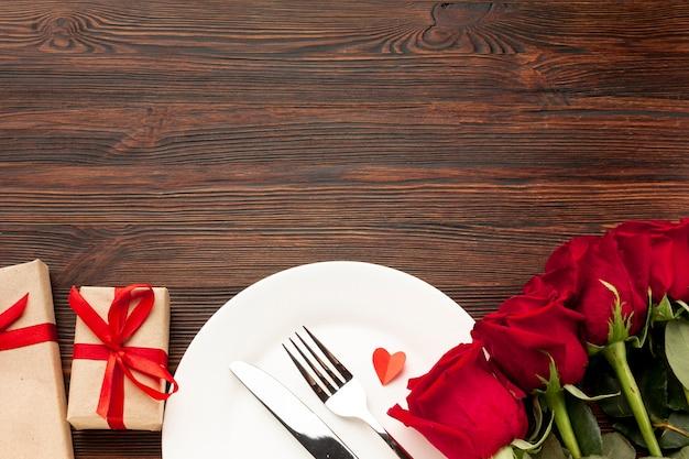 Reizende anordnung für valentinstagabendessen auf hölzernem hintergrund mit kopienraum