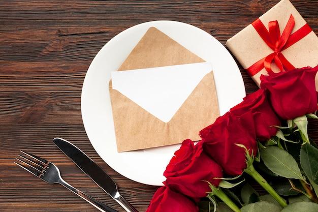 Reizende anordnung für valentinstagabendessen auf hölzernem hintergrund mit umschlag