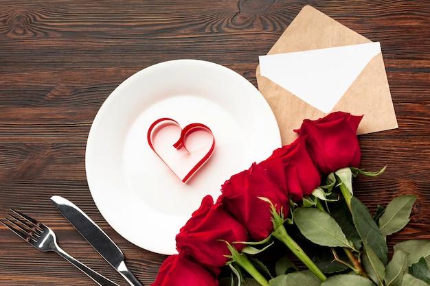 Reizende anordnung für valentinstagabendessen auf hölzernem hintergrund