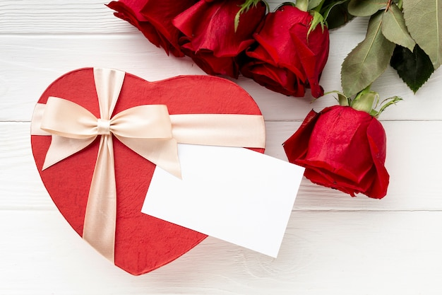 Reizende anordnung für valentinstagabendessen auf weißem hölzernem hintergrund