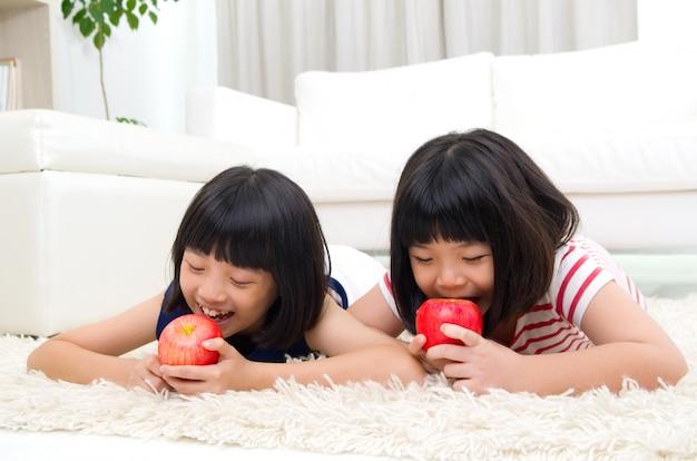 Reizende asiatische mädchen, die apfel essen