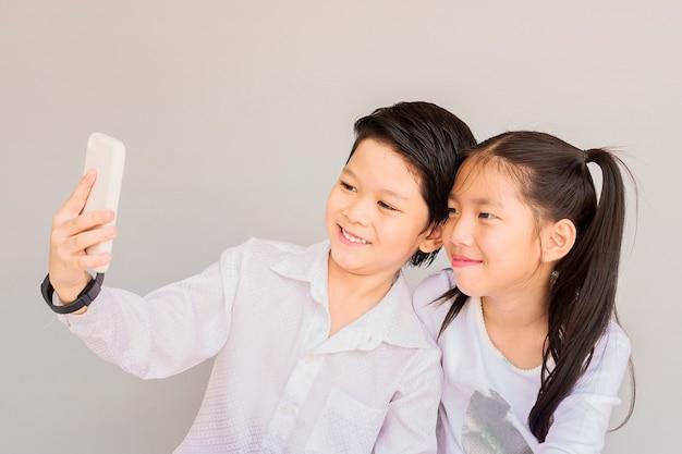 Reizende asiatische paarschulkinder nehmen selfie