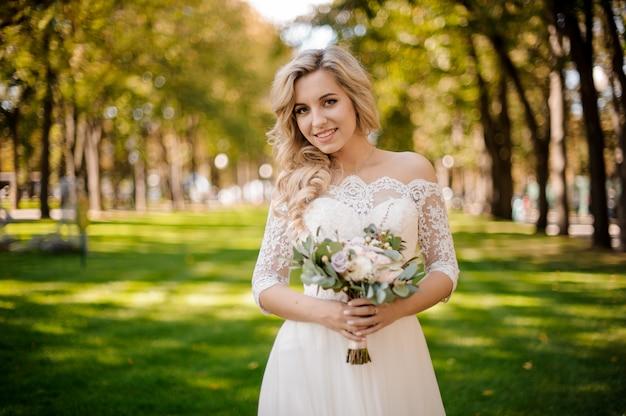 Reizende blonde braut kleidete in einem schönen kleid an, das auf dem rasen steht