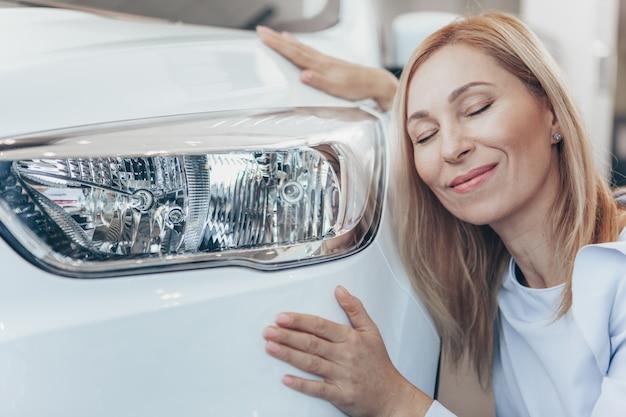 Reizende fällige frau, die ihr neues automobil umarmend lächelt