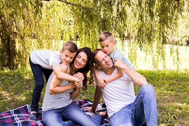Reizende familie, die auf picknickdecke spielt