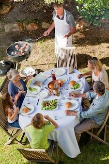 Reizende familie, die im garten isst