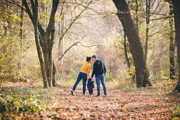 Reizende familie im herbstpark, junge eltern mit den netten entzückenden kindern, die draußen spielen. glückliche familie genießen sie die herbstliche natur. glückliche familie und sie söhne, die in herbstpark gehen und eine schöne zeit haben