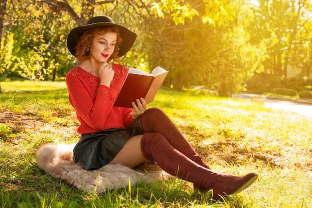 Reizende frau, die ein buch im herbstpark sitzt auf dem gras liest