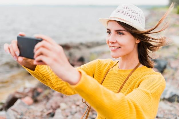Reizende frau, die ein selfie in dem meer nimmt