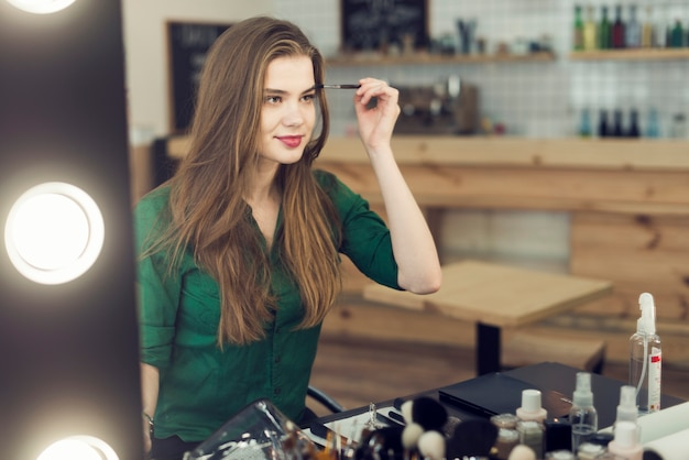 Reizende frau, die kosmetik auf augenbrauen anwendet