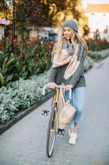 Reizende frau, die mit fahrrad nahe blumenbeet geht