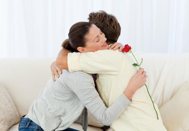 Reizende frau, die seinen freund umarmt, nachdem er eine blume empfangen hat
