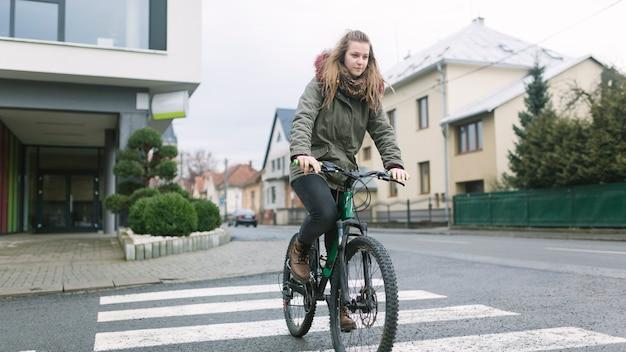 Reizende frau, die straße auf fahrrad kreuzt