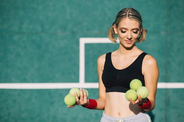 Reizende frau, die tennisbälle hält