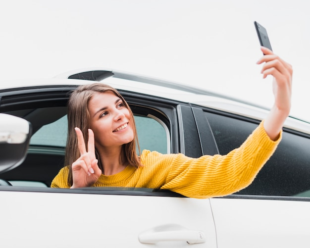 Reizende frau im auto, das ein selfie nimmt