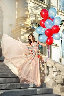 Reizende frau im schönen kleid mit bunten ballonen