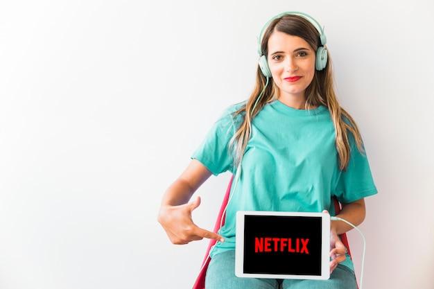 Reizende frau in den kopfhörern zeigend auf netflix-logo