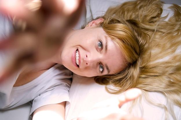 Reizende frau nach dem erwachen glücklich für den neuen tag lächelnd im bett