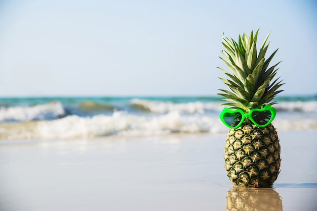 Reizende frische ananas setzte herzformsonnenbrillen auf sauberen sandstrand mit seewelle - frische frucht mit meersandsonnen-ferienkonzept