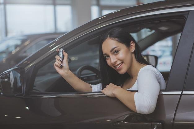 Reizende junge frau, die neues auto an der verkaufsstelle kauft