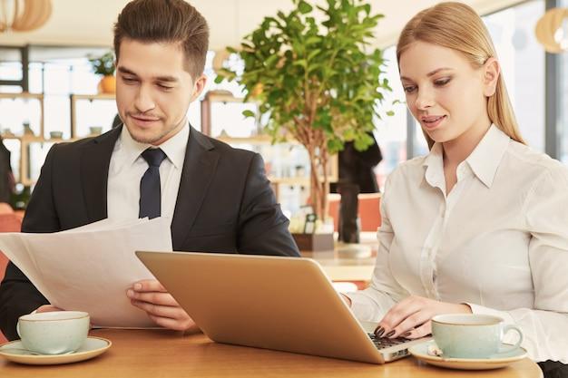 Reizende junge geschäftsfrau, die auf ihrem laptop während des geschäftstreffens mit männlichem kollegen schreibt