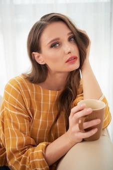 Reizende junge kaukasische frau, die zu hause auf couch mit tasse kaffee aufwirft