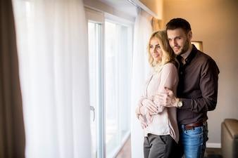 Reizende junge Paare, die das Fenster im Raum bereitstehen