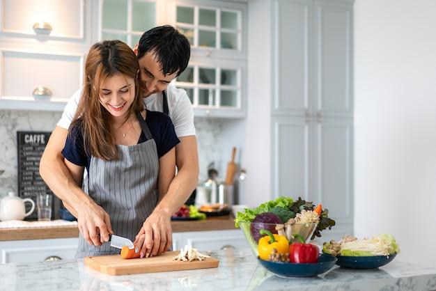 Reizende junge paare, die gesunde mahlzeit in der modernen küche zubereiten. bemannen sie das umarmen der frau, die am morgen an der küche romantisch ist.