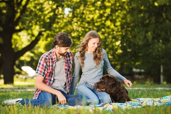 Reizende junge Paare, die mit ihrem Hund im Garten sitzen