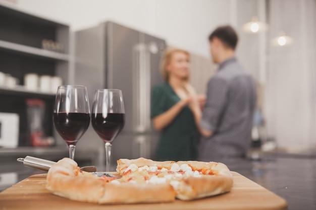 Reizende junge paare, die zusammen pizza an der küche essen