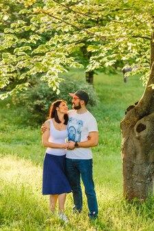 Reizende junge romantische Paare, die auf grünem Gras unter dem Baum stehen