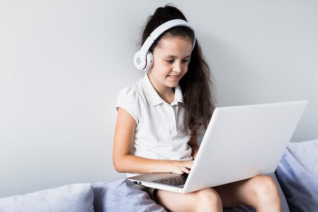 Reizende kleine mädchen, die ihren laptop verwenden