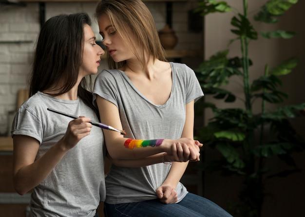 Reizende lesbische frau, welche die regenbogenflagge auf der hand ihrer freundin mit malerpinsel malt