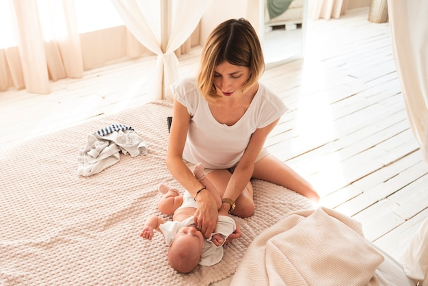Reizende mutter, die neugeborenes baby kleidet