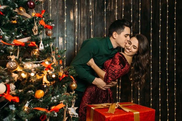 Reizende paare in der liebe, die nahe weihnachtsbaum umfasst