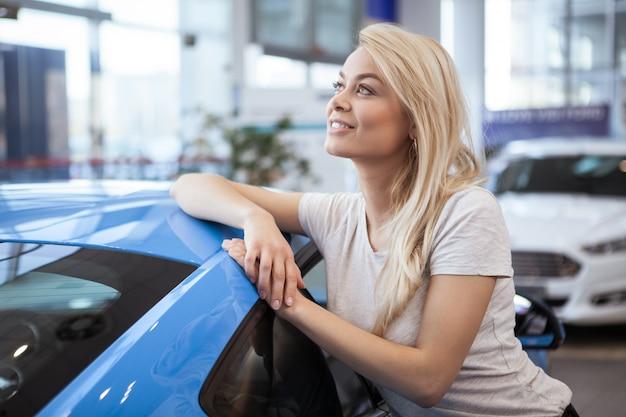 Reizende schöne frau, die auf einem neuen automobil an der verkaufsstelle weg schaut sich lehnt