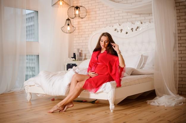 Reizende schwangere frau im rosa negligé, das auf dem bett sitzt