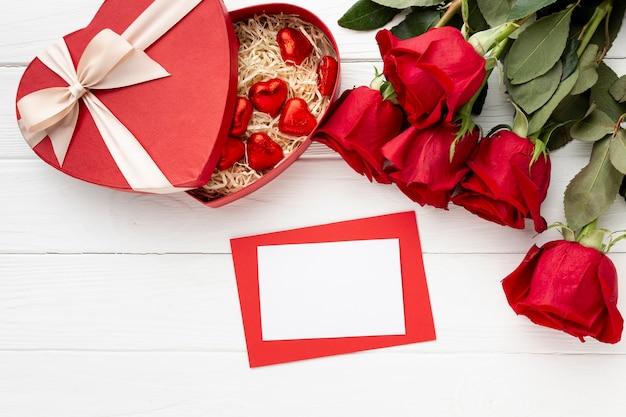 Reizende zusammenstellung für valentinstagabendessen auf weißem hölzernem hintergrund mit leerer karte