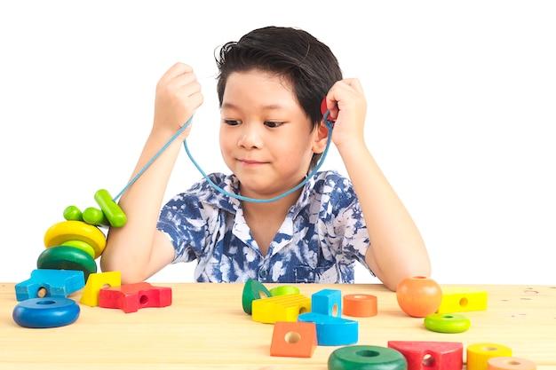 Reizender asiatischer junge ist buntes hölzernes blockspielzeug des spiels