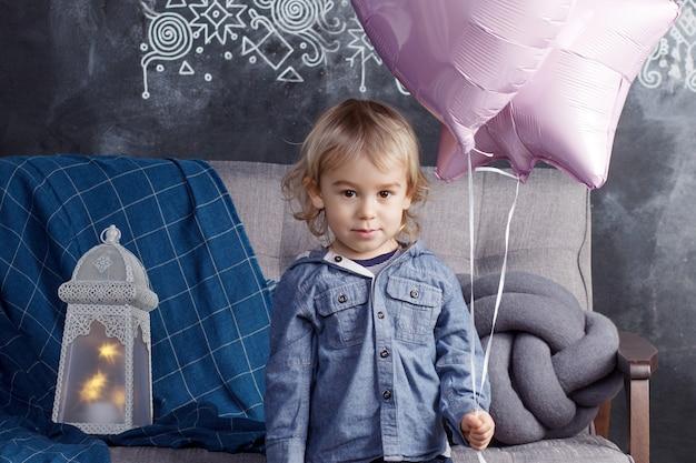 Reizender junge, den die blondine mit ballonen spielt.