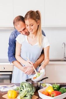 Reizender junger mann, der seine frau liebt, die das lebensmittel in der küche zubereitet