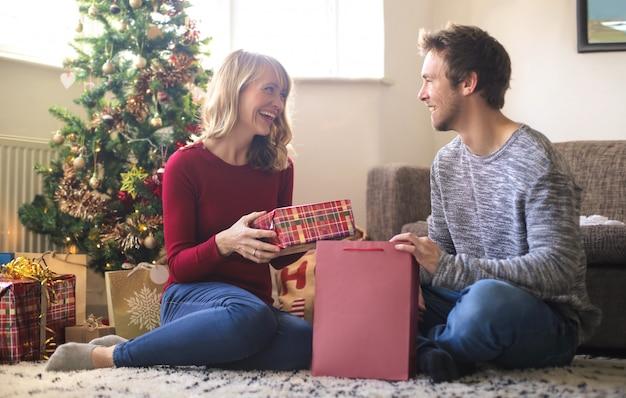 Reizender kerl, der ihrer frau sein weihnachtsgeschenk gibt