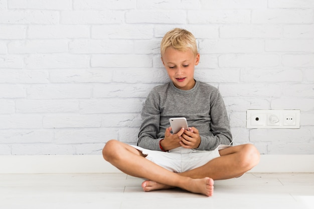 Reizender kleiner junge, der seinen smartphone verwendet