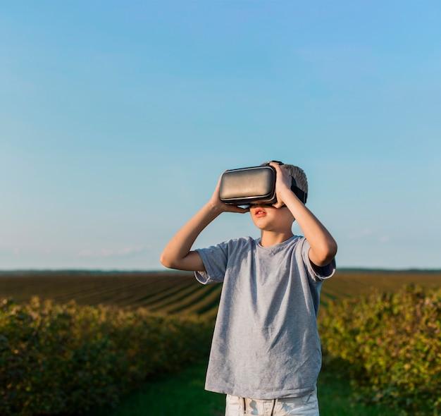 Reizender kleiner junge, der spaß mit gläsern der virtuellen realität hat