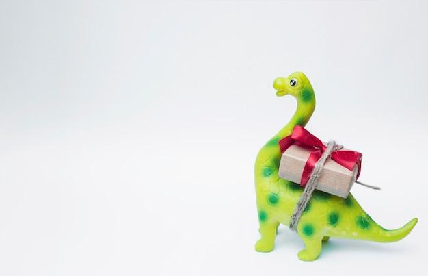Reizender spielzeugdinosaurier mit weihnachtsgeschenk