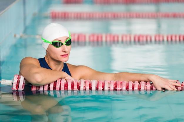 Reizender weiblicher schwimmer, der mittleren schuss aufwirft