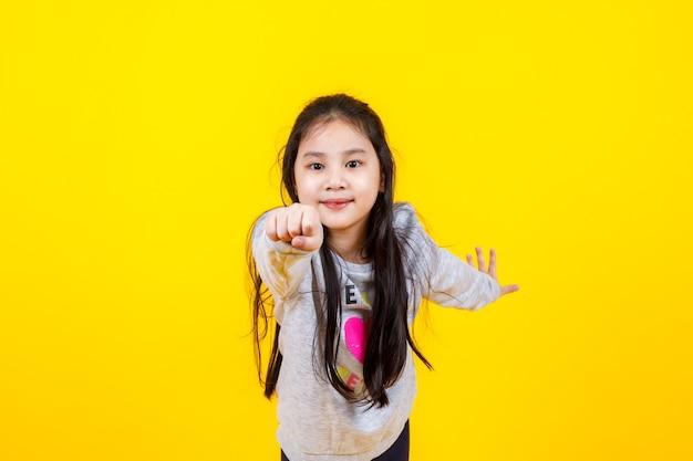 Reizendes asiatisches mädchen, das pullover trägt, lächelt und genießt es, die hand mit den fingern auf die kamera zu zeigen.
