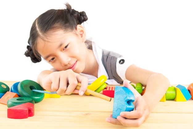Reizendes asiatisches mädchen ist buntes hölzernes blockspielzeug des spiels