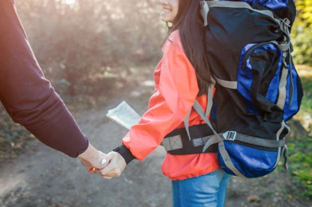 Reizendes bild des händchenhaltens des jungen mannes und der frau zusammen. sie hat einen rucksack auf dem rücken und eine karte auf den händen. sie gehen zusammen.
