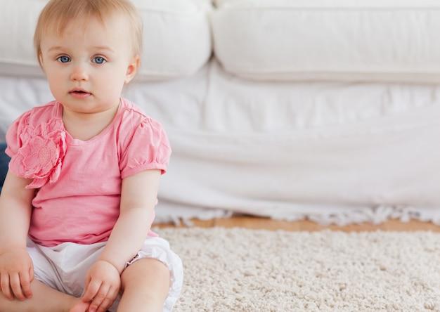 Reizendes blondes baby, welches die kamera beim sitzen auf einem teppich betrachtet
